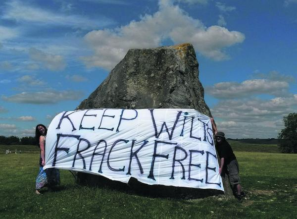 Anti-fracking campaigners Becky Martin and Clive Humphries unveil a banner at Avebury