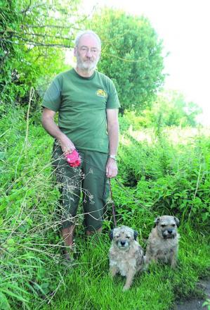 Adrian Bass at one of the  overgrown footpaths with his border terriers Oscar and Tasha