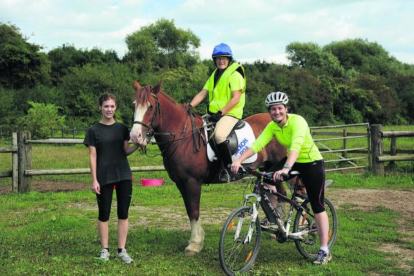 RDA instructors Jo Rutherford, mounted on Chesney, and Kady Chatman on her bike, with runner Holly Rutherford, after their 50-mile challenge