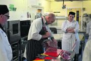 Shawn Byrne demonstrates his butchery technique on one of student Olly Lander's lambs