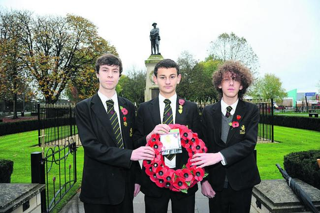 Clarendon year 11 pupils Morgan, Ollie and Ellis with their wreath they laid at the Trowbridge War Memorial.                         (50622)