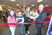 Elise Ford prepares to cut the ribbon watched by Ethan and Phoenix Bolton with store manager Michael Corr.