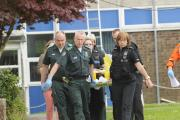 Paramedics and police carry the stretcher of the boy who fell through a glass skylight at Clarendon Academy. Picture by Trevor Porter