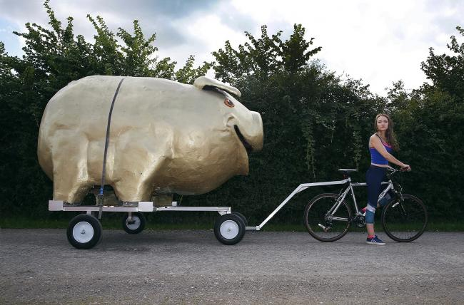 Rosie-Mae Iredale with the giant piggy bank which she hopes will be travelling through Wiltshire on Monday and Tuesday