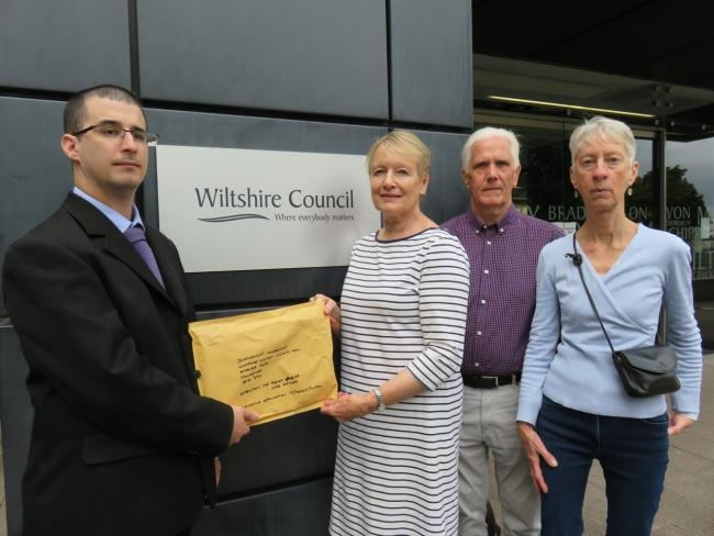 Kieran Elliott of Wiltshire Council democratic services takes the petition from Chris Leyland, Keith Leyland and Celia Hollingworth. Photo: Helen Murray