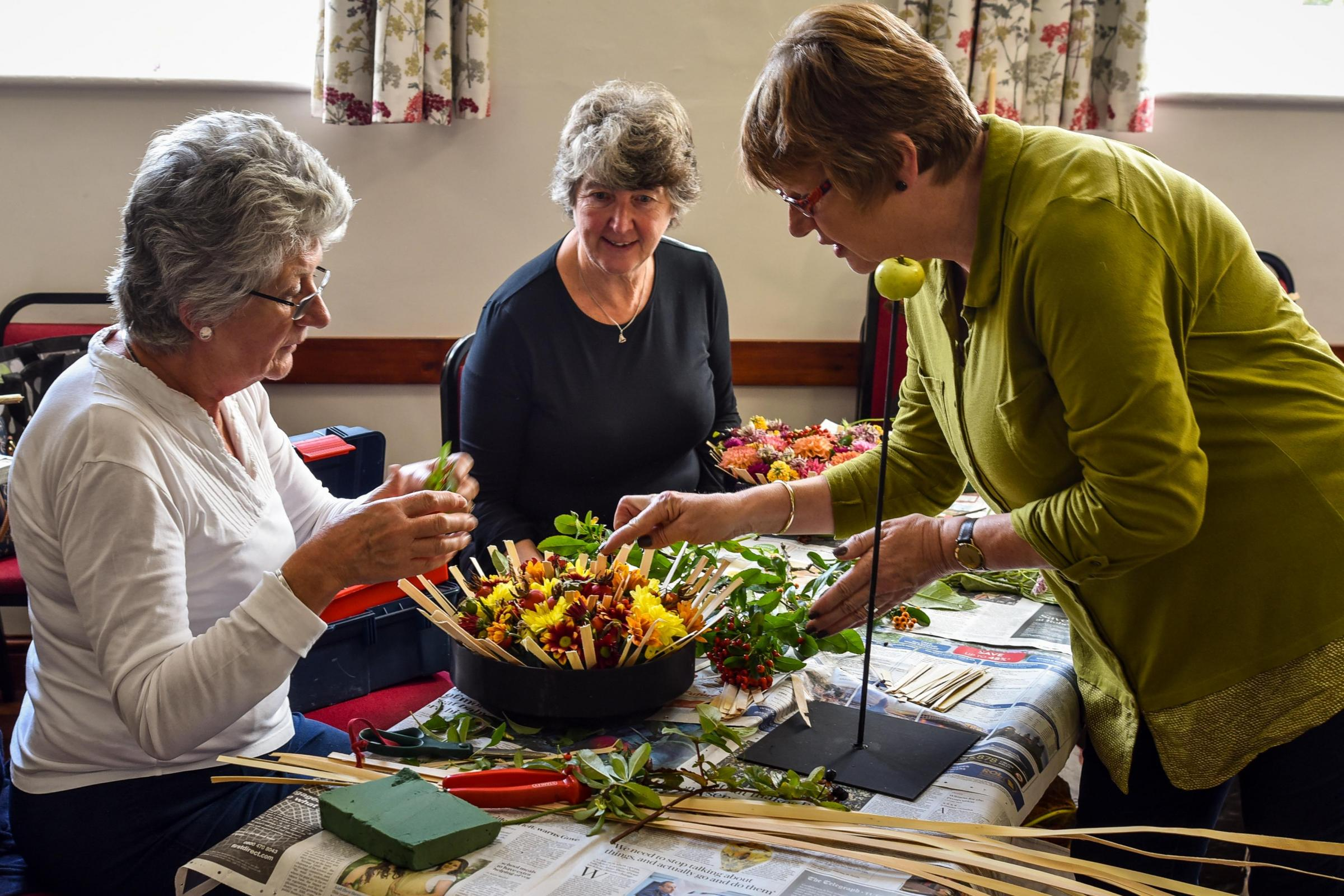 National floral designer Angela Turner (right) working with Liz Harris and Sharon Ecob at Bradford on Avon & District Flower Club's workshop and demonstration at Holt Village Hall on Saturday. Photo www.gphillipsphotography.com GP1061.