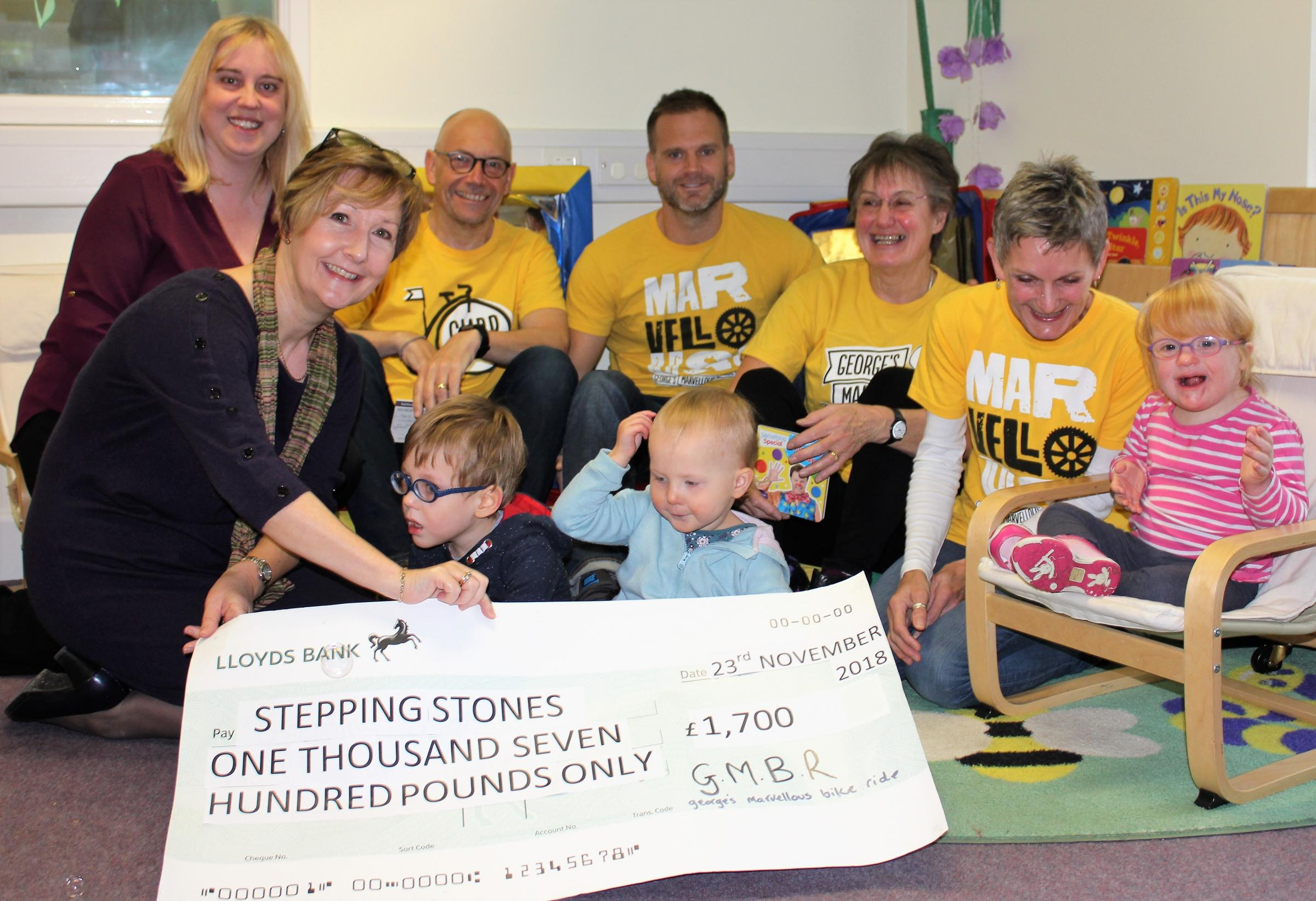 Anna Hutchings, of George's Marvellous Bike Ride, hands over the £1,700 cheque to Stepping Stones