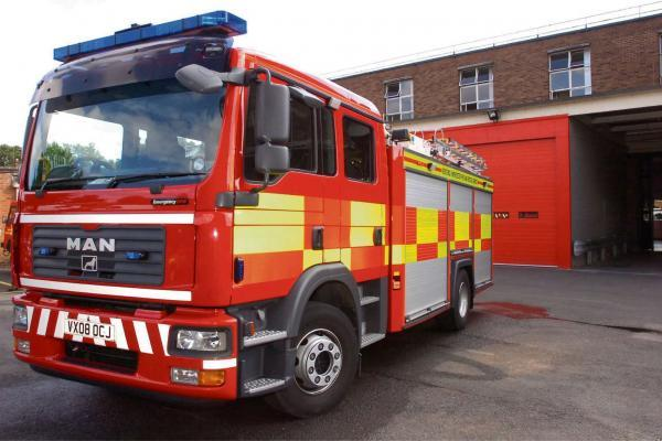 Firefighters use buckets of water on hedge blaze