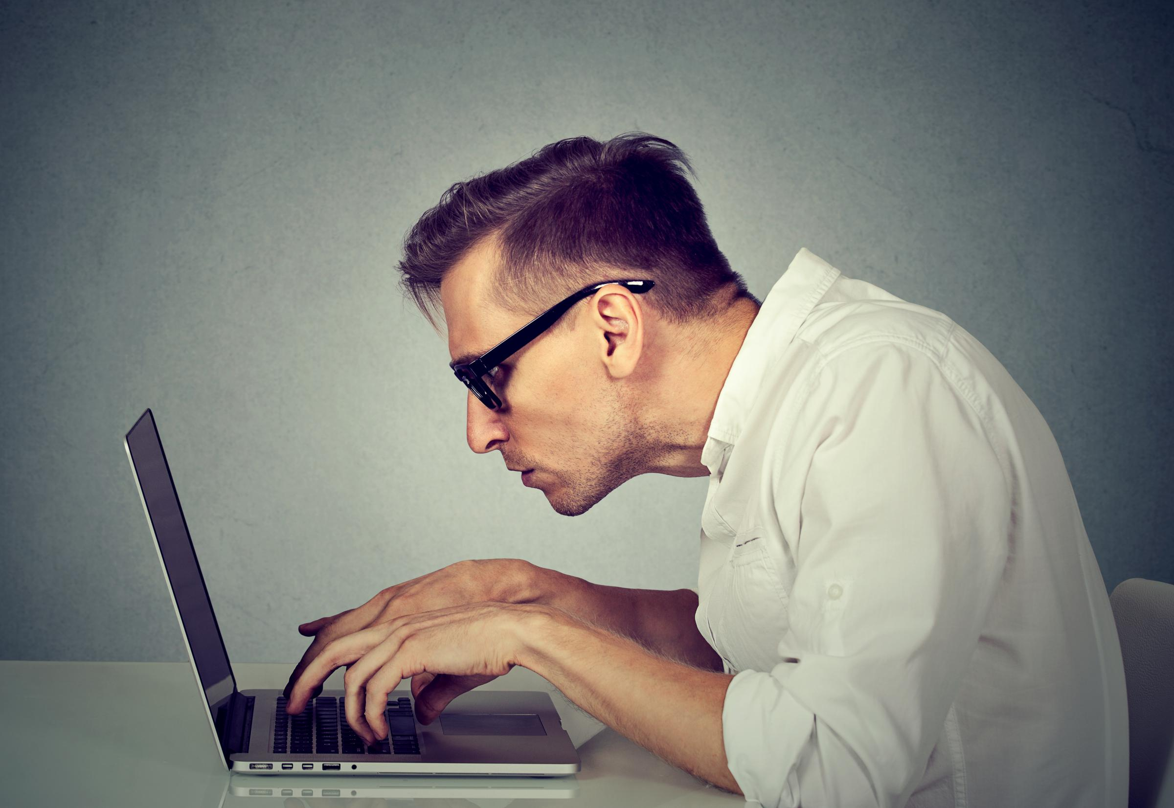 Side profile young man in glasses working on computer sitting at desk isolated on gray wall office background. Long monotonous tiresome working hours life concept.