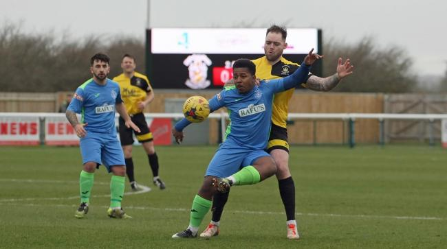 Action from the 3-2 win for Melksham Town (yellow) over Highworth Town on Saturday, March 16, 2019 - Greg Tindle (Melksham) and Yeshaya Lomotey (Highworth) - PICTURE: ROBIN FOSTER